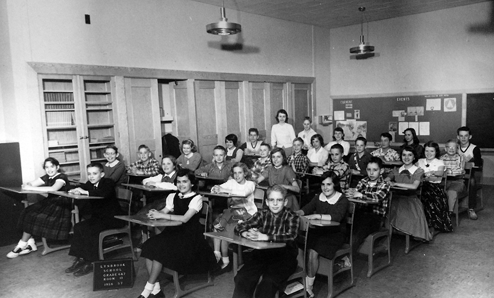 Black and white class photograph taken during Lynbrook's first year of operation. The students are seated on metal chairs with book storage beneath the seat and an attached writing surface. They are arranged four rows across and seven rows deep. The boys are wearing button down plaid shirts or suits with ties, and the girls are wearing dresses or skirts. The teacher can be seen standing at the back of the room.