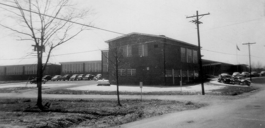 Black and white photograph of Garfield Elementary School taken in 1954 for a fire insurance survey for the Fairfax County School Board. The picture was taken from Old Keene Mill Road and faces the east side of the building. This side of the school looks very similar today, except the main entrance has been moved to face Spring Road.