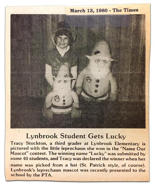 Photograph of an article from The Times newspaper printed on March 13, 1980. A little girl is kneeling next to two leprechaun stuffed figures. The photograph caption reads: Lynbrook Student Gets Lucky. Tracy Stockton, a third grader at Lynbrook Elementary is pictured with the little leprechaun she won in the Name Our Mascot contest. The winning name, Lucky, was submitted by some 40 students, and Tracy was declared the winner when her name was picked from a hat – St. Patrick style of course. Lynbrook's leprechaun mascot was recently presented to the school by the PTA.