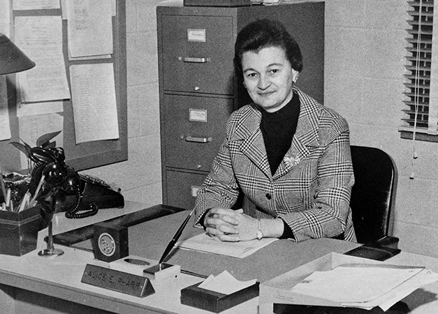Black and white portrait of Principal Pharr taken in 1976. She is seated at her desk with her hands folded. A filing cabinet is visible behind her. On the desk are a rotary dial phone, a name place, and stacks of paperwork.