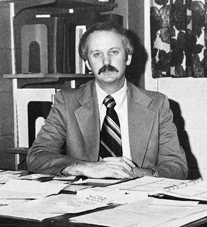 Black and white portrait of Principal Bender taken in 1981. He is seated at his desk which is covered with paperwork. A bookshelf is visible behind him.