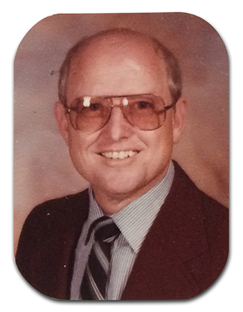Color head-and-shoulders portrait of Principal Huffman taken in 1985. The edges of the picture are rounded.