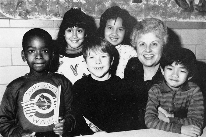 Black and white portrait of Principal Eaton taken in 1989. She is seated, surrounded by a group of six smiling students.