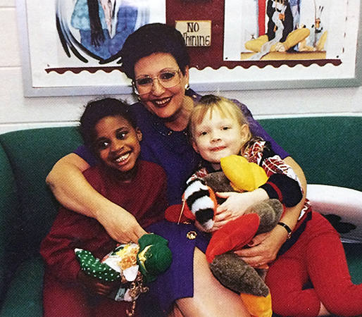 Color portrait of Principal Brower taken in 1995. She is seated on a green sofa with two smiling children and has her arms wrapped around them. The children are holding assorted stuffed animals.