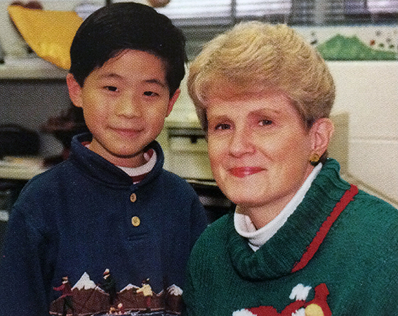 Color portrait of Principal Walters taken in 1997. She is pictured with a male student in her office.