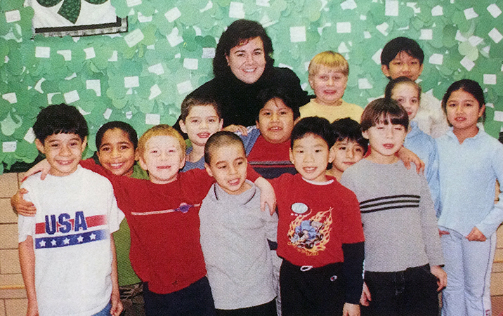 Color portrait of Principal Aste taken in 2003. She is standing in a hallway behind a large group of smiling students. 13 children are pictured, all but two of whom are male.