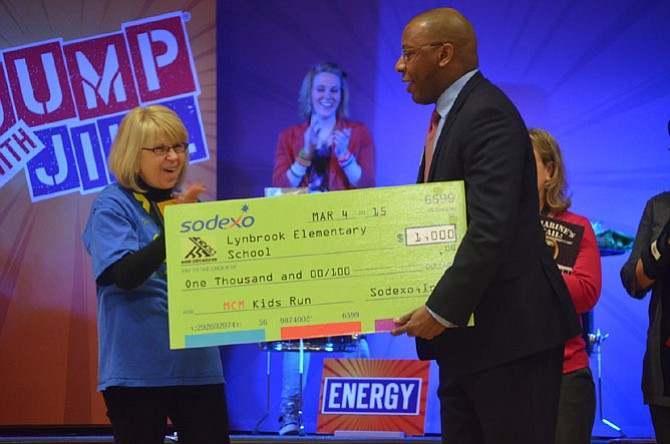 Color portrait of Principal McNamee taken in 2015. She is on stage at an event accepting a giant green check for $1,000 from a tall gentleman representing Sodexo, Inc.